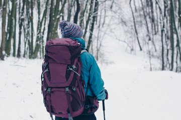 Young girl with backpack hiking downhill through the winter forest. Look from the back
