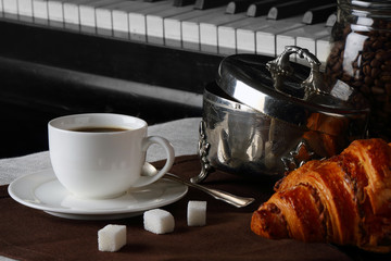 Cup of coffee with croissants on piano background