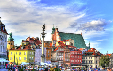 Colorful HDR image of the tourists at the famous Old town in Warsaw, Poland. The Royal Castle and Sigismund's Column called Kolumna Zygmunta, Warsaw, Poland