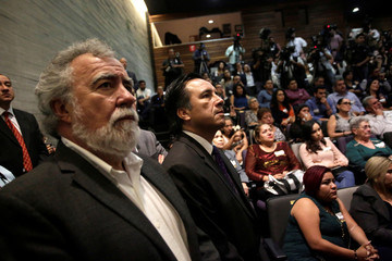 Subsecretary of Human Rigths and Governor of Veracruz watch a screen in a public apology offered to relatives of five youths killed in 2016 after police kidnapped them and then turned them over to members of a drug gang, in Mexico City