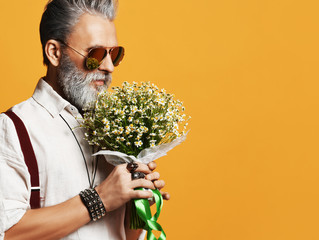 Brutal senior bearded old man in aviator sunglasses ready to give a bouquet of chamomile daisies on yellow
