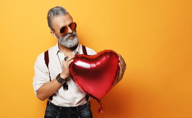 Senior bearded old man in aviator sunglasses holds gently red heart balloon for valentines day on yellow background