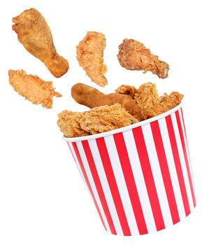 Perfect fried chicken pieces flying around in red white striped box