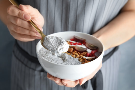 Young woman eating tasty chia seed pudding, closeup