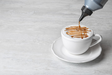Adding caramel topping to latte macchiato on table, space for text