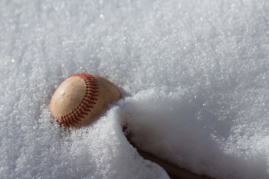Baseball stuck in fluffy white snow during winter season