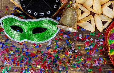 Purim jewish holiday with purim mask and purim a noisemaker on a vintage wood background with copys pace