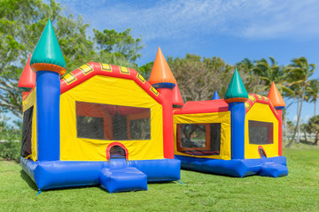 Two multi-color castle bounce houses are ready for the kids. A beautiful sunny is the perfect time to set up bounce houses at the local park.