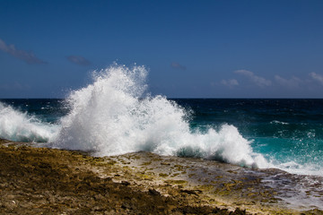 Wild and high waves breaking at the rough shoreline of the west coast of the island of Bonaire