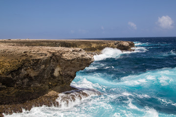 Wild and high waves breaking at the rough cliffs on the east coast of the tropical island of Bonaire in the caribbean