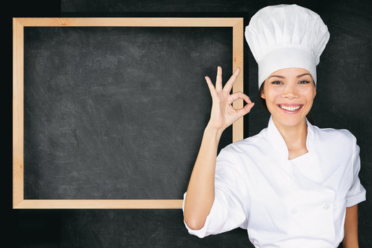 Happy chef doing perfect okay hand sign at empty menu black board background. Asian woman in front of blank menu blackboard. Cook or baker showing chalkboard menu wearing chef whites uniform and hat