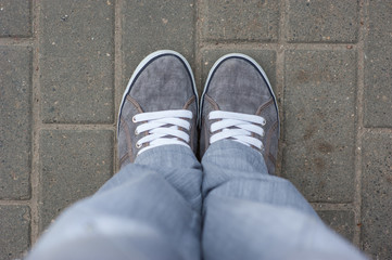 Gray sneakers with white laces stand on the tile, top view, comfortable shoes for walking around the city. gray bottom clothes