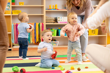 Nursery babies play on floor with carers or mothers in day care centre
