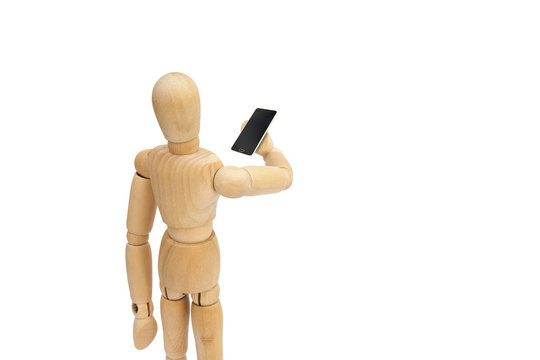 Wooden figure mannequin holding black smartphone isolated on white background.