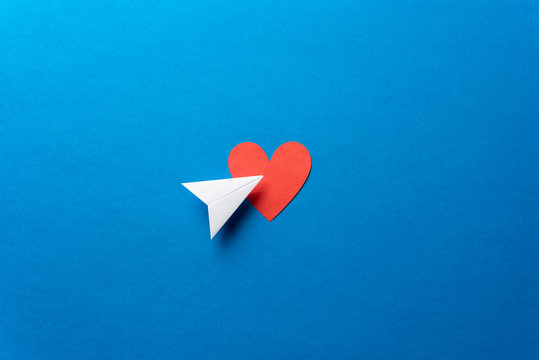 Paper plane with red heart shape on blue background. Sharing and send concept.