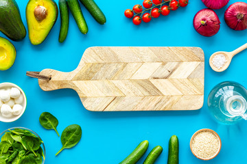 Fresh organic vegetables on blue background top view space for text. Kitchen desk for preparing salad. mockup with cutting board