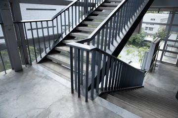 Empty concrete staircase with black steel handrail.