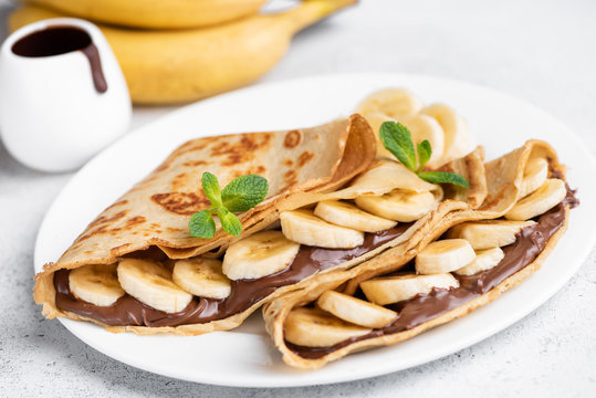 Crepes stuffed with chocolate spread and banana on white plate. Thin pancakes, blini. Sweet dessert.