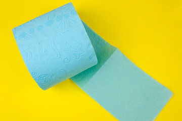 roll of blue  toilet paper on a yellow background
