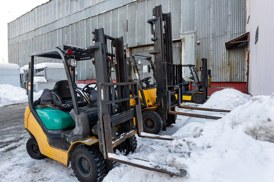 Several forklifts stand near the warehouse building.