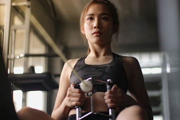 Close Up of a young woman exercising at the gym with fitness machines.