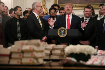 President Trump speaks behind stacks of hamburgers and other fast food during event with North Dakota State University football team at White House in Washington