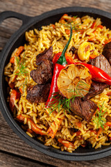 The concept of oriental cuisine. National Uzbek pilaf with meat in a cast-iron skillet, on a wooden table. background image. top view, copy space, flat lay