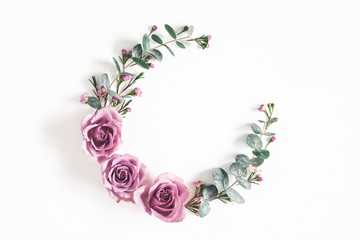 Flowers composition. Wreath made of eucalyptus branches and rose flowers on white background. Flat lay, top view, copy space