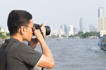 A man taking photos at the river with surrounding tall buildings and tree in distance