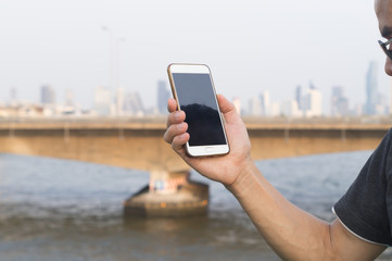 A man holding his smartphone to get signal on the bridge