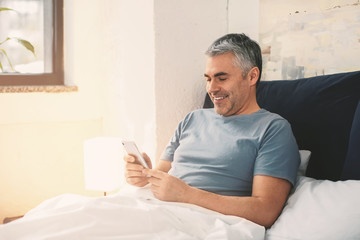 Mature man with mobile phone in bed