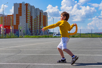 the boy throws a boomerang into the blue sky. The kid plays with a boomerang on the Playground. children's outdoor sports games