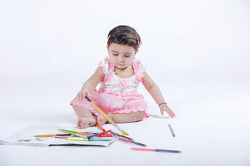 Cute little Indian/Asian Girl enjoying Painting  with paper, colour pencle and art brush