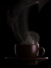 Silhouette coffee cups with saucer and hot steam isolated on black