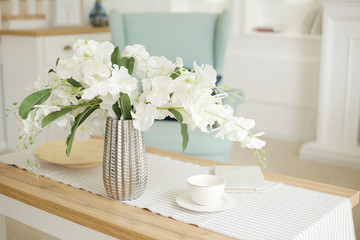 Light classic living room interior. coffee table and white orchid in vaz. A bright sunny day