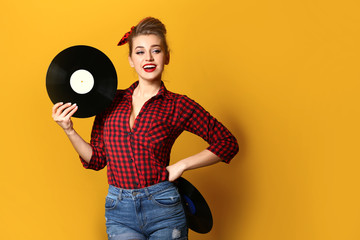 Beautiful pin-up woman with vinyl discs on color background