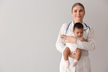 Pediatrician with African-American baby on light background
