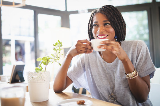 Beautiful young african woman enjoying a cup of coffee while relaxing at coffee shop