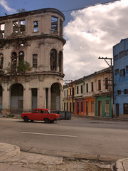 Facade of classic old heritage building under bright blue sky and white clouds in downtown Havana, Cuba with plants growing from window, red car and road in foreground, and colorful row houses in back