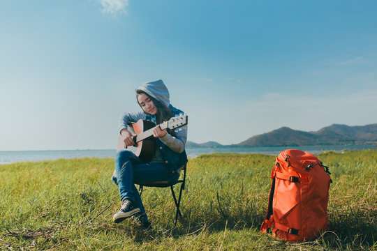 Asian woman teenager playing guitar resting outdoor in trekking with backpack at sunset happiness.