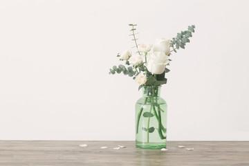 Obraz eucalyptus twigs and roses  in  glass vase on white background - fototapety do salonu
