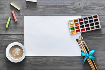 Artist wood gray background concept, creative painting lesson art work supplies paper, paint brushes, paintbox with watercolors coffee on grey wooden table, creativity flat lay top view copy space