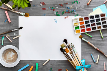 Artistic background concept, creative art work accessory colorful supplies set, paper, paint brushes, paintbox with watercolors on grey wooden table, drawing education, top view, flat lay, copy space