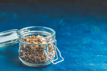 Open glass jar of organic granola on a dark blue concrete table