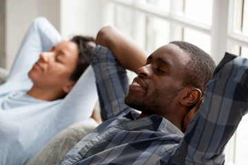 Happy black couple relax on couch hands over head