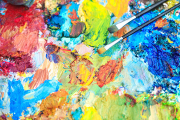 Color background of the artist's palette with brushes.