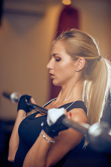 Close up of woman lifting weight bar. Gym interior. Healthy lifestyle concept.