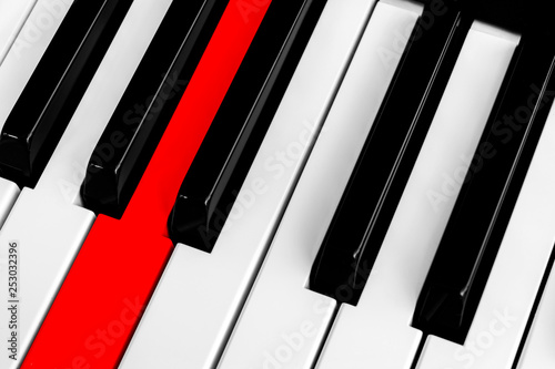 Top view of piano keys with one red button  Close-up of piano keys