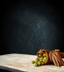Beer, brewery background. Fresh green hop and wheat with wooden barrel on vintage table. Ingredients for brewing. Retro style. Beer brewing traditions. Copy space for your text