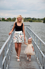 Mother and daughter are walking, having fun, playing in the park, on the banks of the river. The concept of family relationships, motherhood.